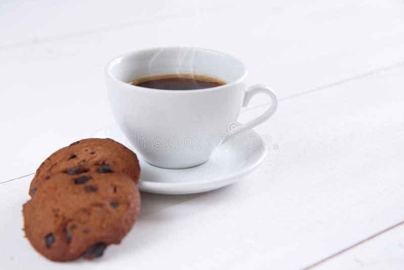 En kopp av doftande kaffe med mjölkar och kakor på den vita bakgrunden royaltyfria foton