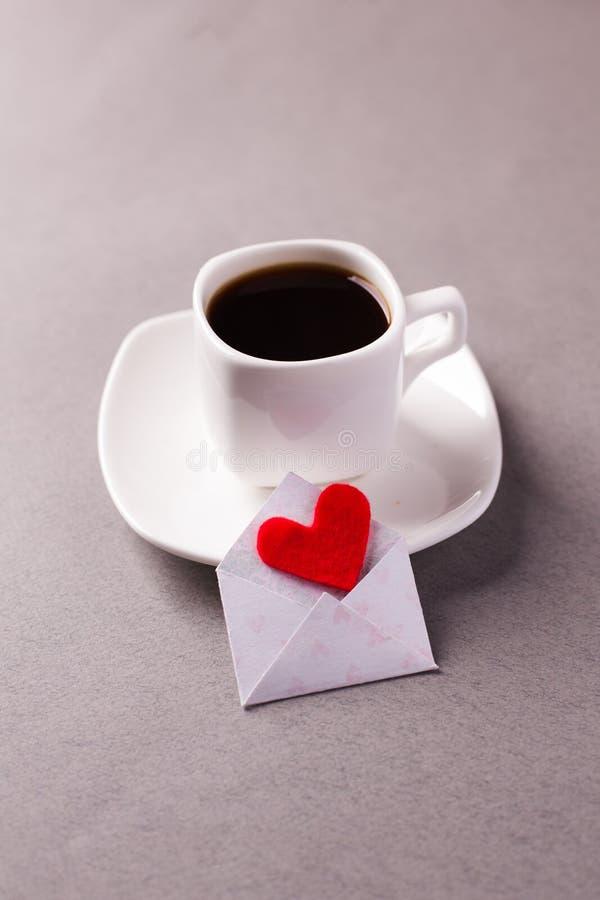 En kopp av espresso på ett tefat och ett förälskelsemeddelande på dag för valentin` s, en förklaring av förälskelse royaltyfri bild