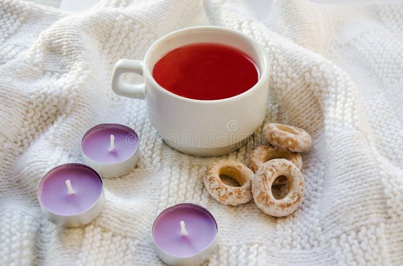 En kopp av fruktsaft, aromatiska stearinljus och baglar på en vit bakgrund royaltyfri foto