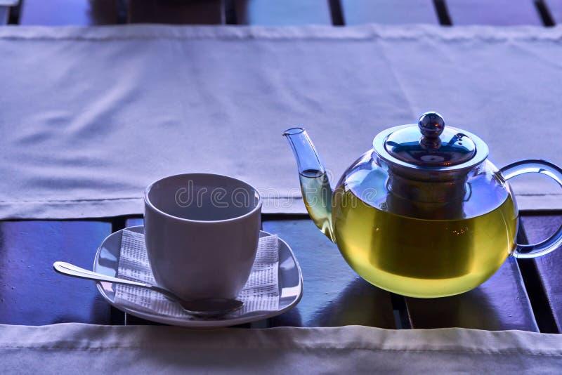 En kopp av grönt te för morgon En genomskinlig tekanna med nytt bryggat grönt te och en vit porslinkopp på tabellen vid windoen arkivbilder