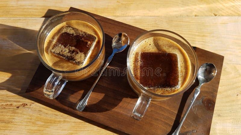 En kopp av kaffe för iskuber på trätabellen arkivbilder