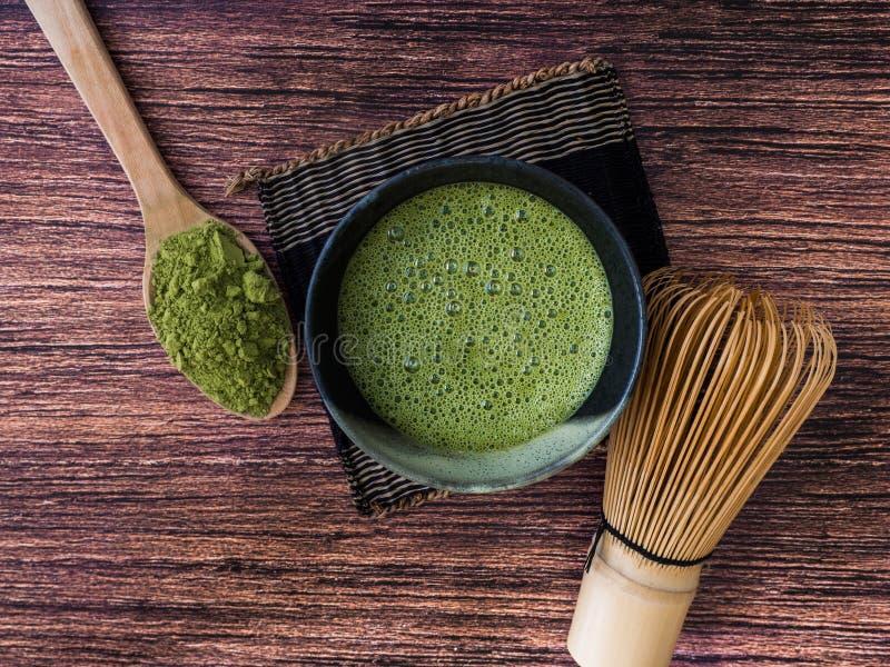 En kopp av latte för grönt te och matchapulver i sked med bambu viftar på träbakgrund royaltyfri foto