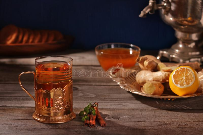 En kopp av ljust rödbrun te, ingefära rotar, tappningsamovar, citronen, kanelbruna pinnar och honung arkivbild