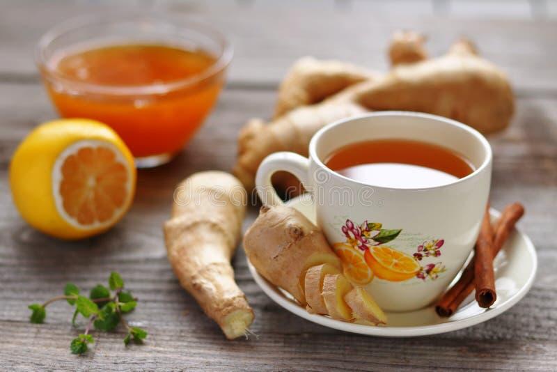 En kopp av ljust rödbrun te som är ljust rödbrun rotar, citronen och honung royaltyfri fotografi