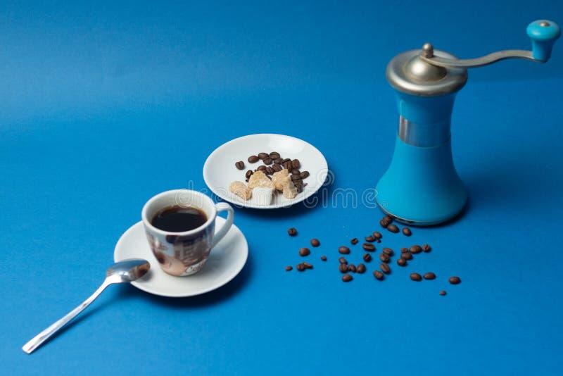 En kopp av svart kaffe med den blåa kaffekvarnen på blå bakgrund arkivbild