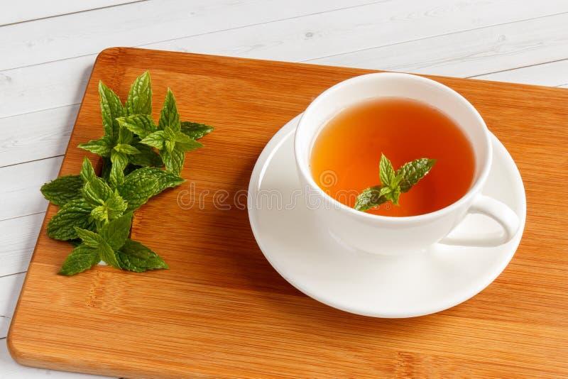En kopp av te för ny mintkaramell på en trätabell med sidor av den nya mintkaramellen, grunt djup av fältet och den selektiva fok royaltyfri foto