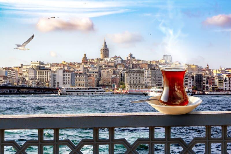 En kopp av turkiskt te i ett traditionellt exponeringsglas mot bakgrunden av det guld- hornet och det Galata tornet i Istanbul arkivfoton