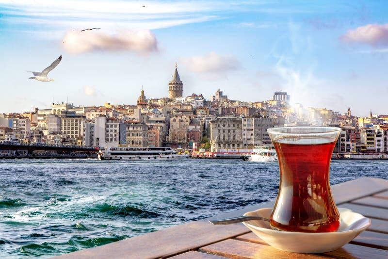 En kopp av turkiskt te i ett traditionellt exponeringsglas mot bakgrunden av det guld- hornet och det Galata tornet i Istanbul arkivfoto