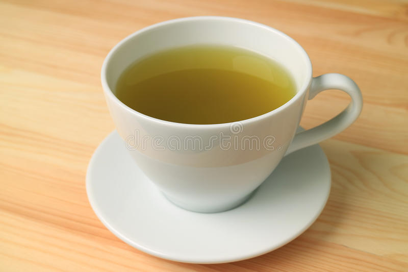 En kopp av varmt grönt te som tjänas som på trätabellen för naturlig färg royaltyfri fotografi