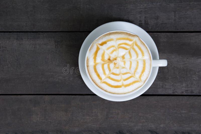 En kopp av varmt kaffe i en vit kopp på träbakgrund Selektiv fokus på ett kopp- och cappuccinoskum Bästa sikt av kaffekoppen av arkivbilder