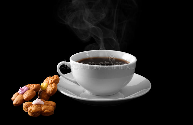 En kopp av varmt kaffe och kakor som isoleras på en svart bakgrund arkivfoton