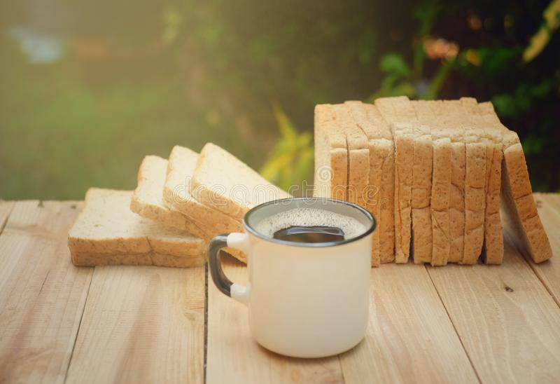 En kopp av varmt kaffe på trätabellen i grön trädgård royaltyfri foto