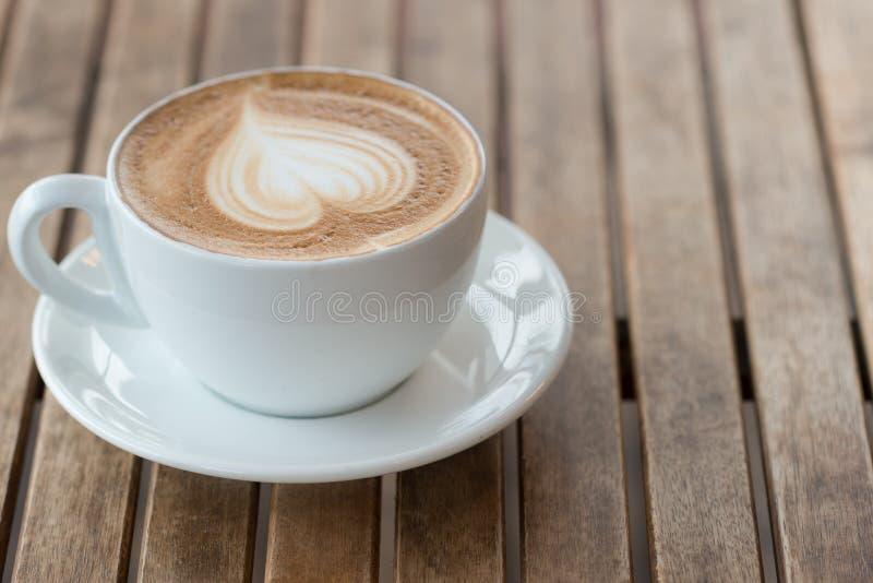 En kopp av varmt latte-, cappuccino- eller espressokaffe med mjölkar skum på den lantliga tabellen Kopiera utrymme f?r text arkivbilder