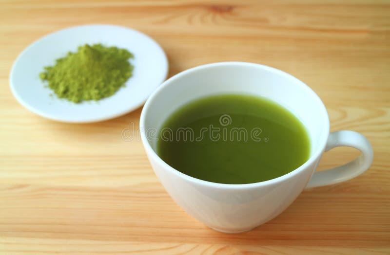 En kopp av varmt Matcha för vibrerande färg grönt te med suddigt Matcha tepulver i bakgrund royaltyfri fotografi