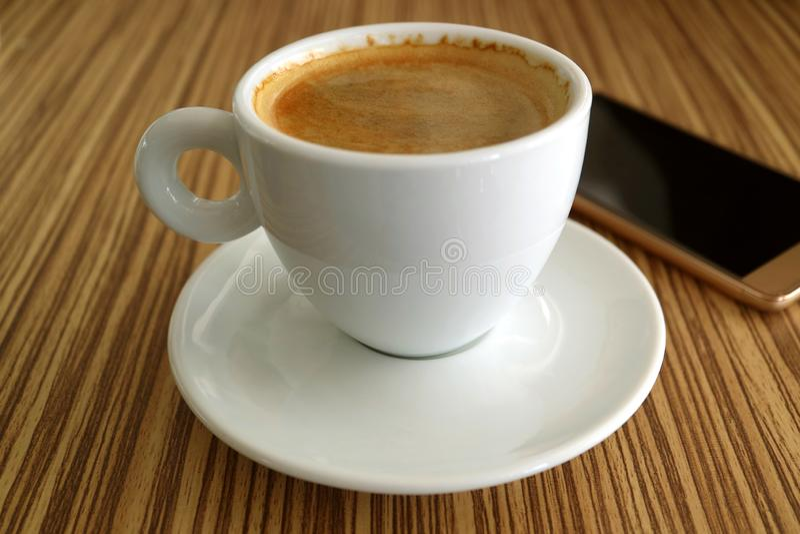 En kopp av varmt svart kaffe med en oskarpa Smartphone i bakgrund arkivbild
