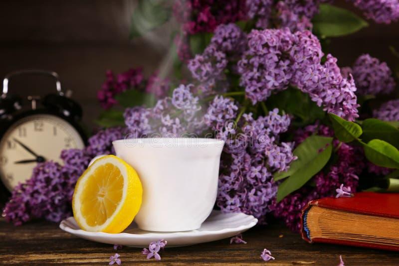 En kopp av varmt te med en citron och över en lila blommar bakgrunden arkivfoton