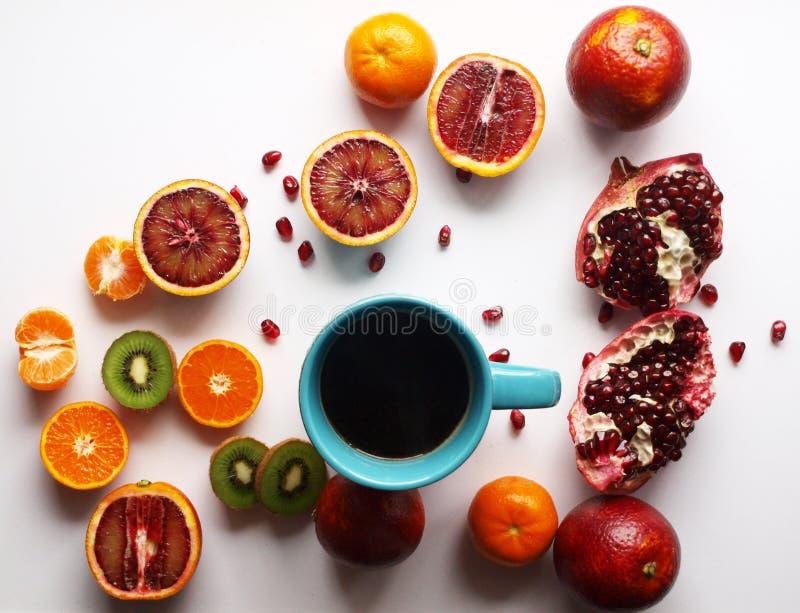 En kopp av varmt te runt om bestrött med tropiska citrusfrukter sommartabell, ljus frukt som är färgrik royaltyfri bild