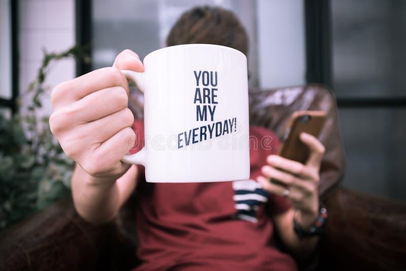 En kopp för grabbhållkaffe med ord är du min dagliga och spela smartphone arkivfoton