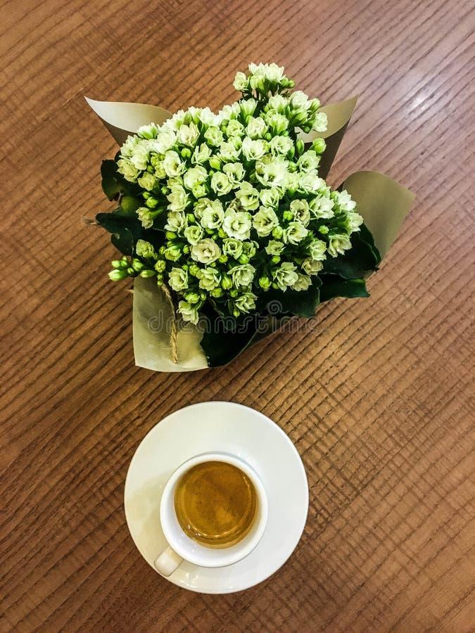 En kopp kaffe med en bukett av blommor royaltyfri foto
