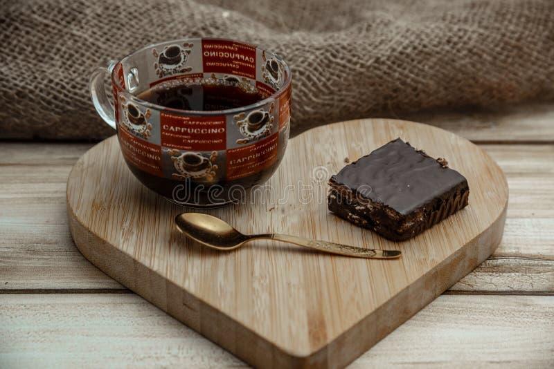 En kopp kaffe med en chokladdillandekaka på ett trähjärta-format magasin royaltyfri foto