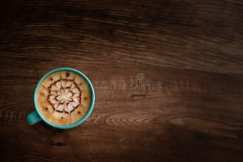 En kopp kaffe med en konstdesign på dess överkant arkivfoto