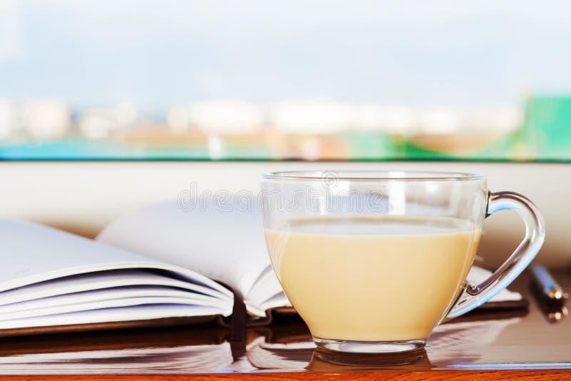 En kopp kaffe med mjölkar och en notepad som ligger på fönsterfönsterbrädan nära fönstret i ottan royaltyfria bilder