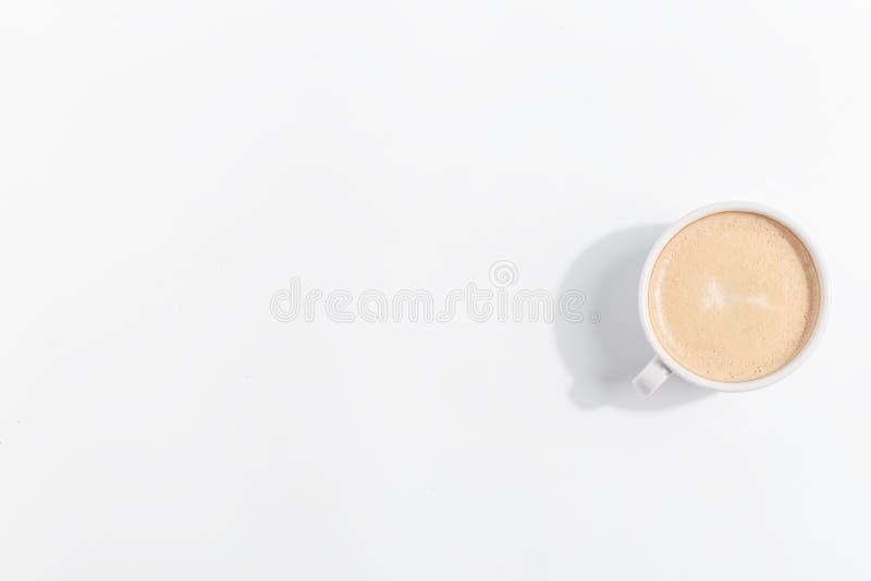 En kopp kaffe med mjölkar på en ljus bakgrund Top beskådar kopiera avstånd arkivfoto