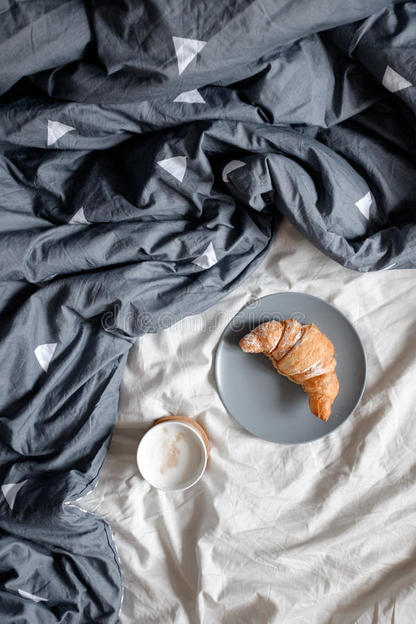 En kopp kaffe och en giffel på en platta på en hemtrevlig säng royaltyfri foto