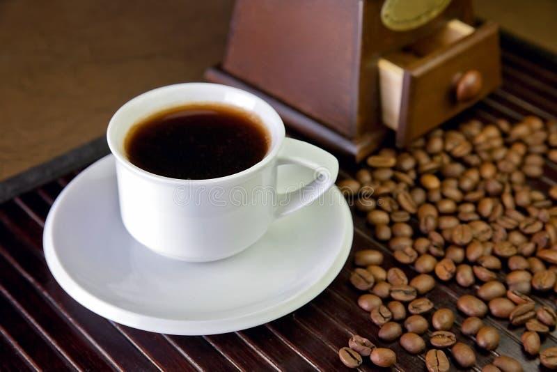 En kopp kaffe och kaffebönor royaltyfria foton