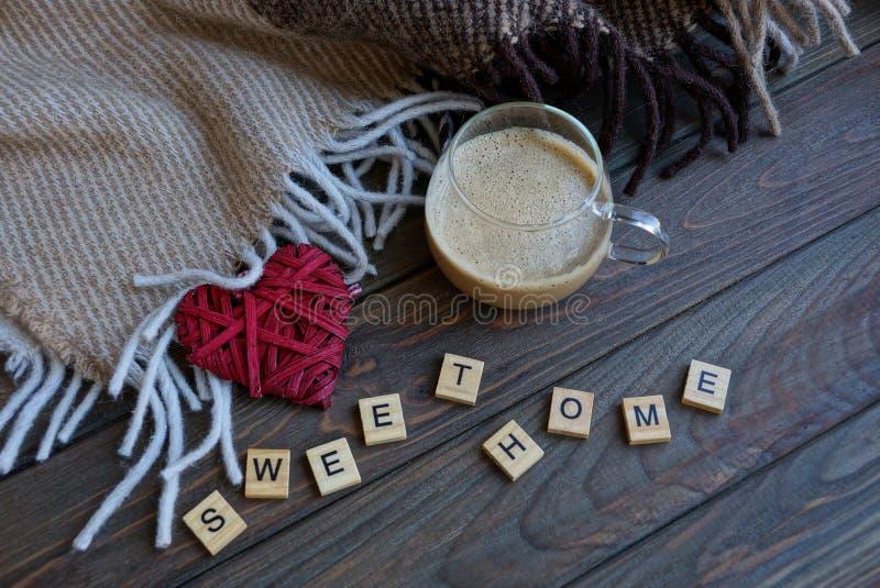 En kopp kaffe och en röd hjärta nära en woolen filt på tabellen med ett ord från träbokstavssötsakhem royaltyfri foto