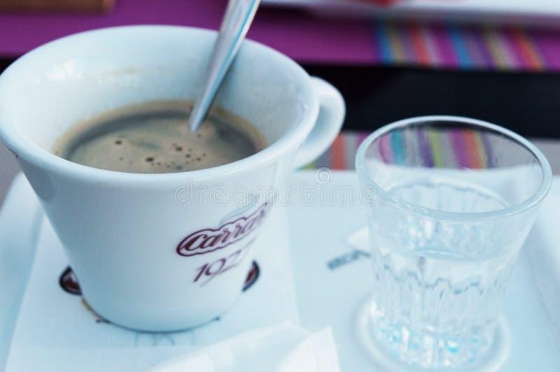 En kopp kaffe och en sked i den med ett exponeringsglas av kallt vatten fotografering för bildbyråer