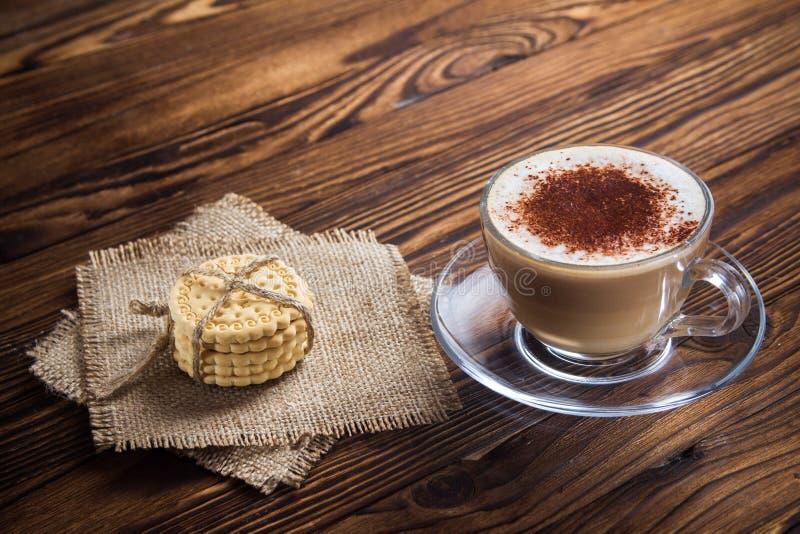 En kopp kaffe och små kakor på en antik trätabell arkivbild