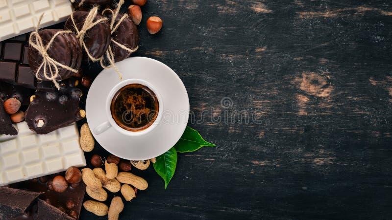 En kopp kaffe och en uppsättning av choklad med kakor och sötsaker På en svart träbakgrund arkivbild