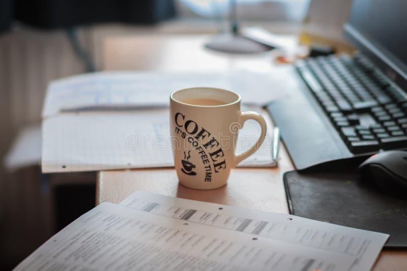 En kopp kaffe på ett arbetsplatsskrivbord Ha ett avbrott av att arbeta eller att lära I framdel står en compter Det kaffetid för  arkivfoton