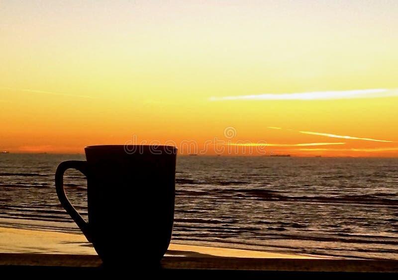 En kopp kaffe på träbalkongräcket på stranden fotografering för bildbyråer