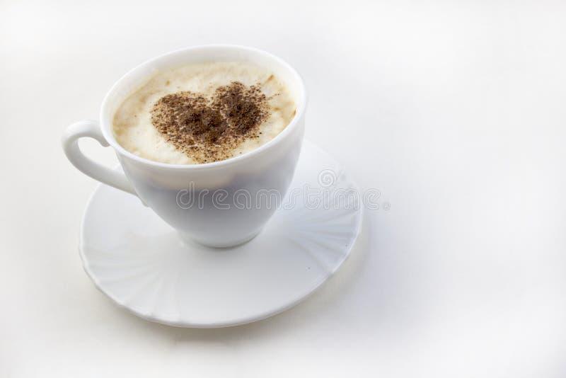 En kopp kaffe på en vit bakgrund som en hjärta gjorde från kanelbrun latte arkivbilder