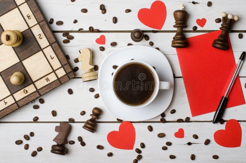 En kopp kaffe, schackstycken och begreppet av förälskelse arkivbilder