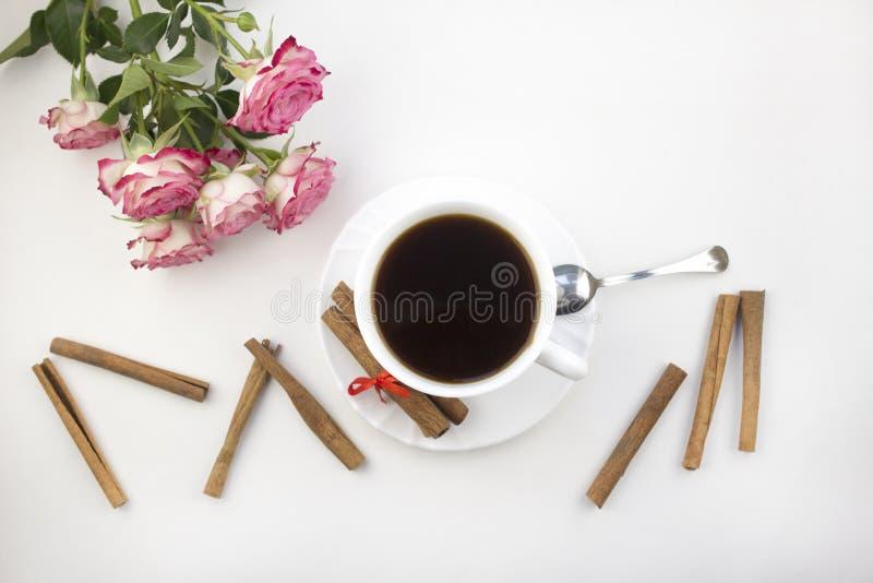 En kopp kaffekanel och rosor på en vit bakgrundsmorgon royaltyfri bild