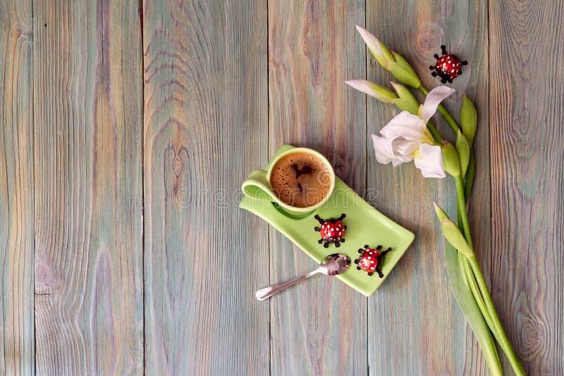 En kopp med morgonkaffe, godisar och en bukett av vita iriers royaltyfri fotografi