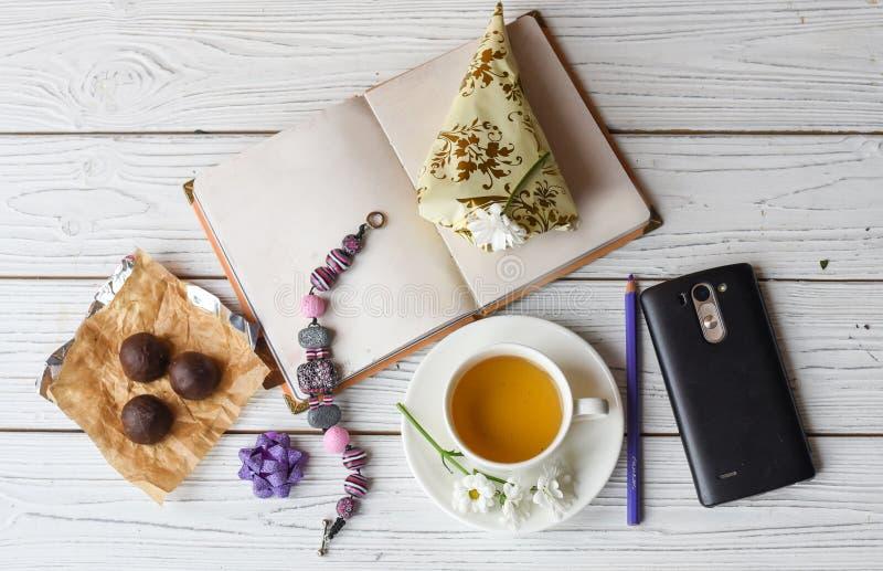 En kopp te, en anmärkningsbok, flera godisar, en halsband nad blommar arkivfoton