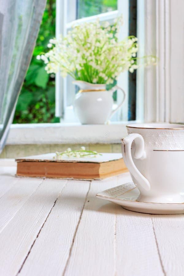 En kopp te eller ett kaffe och en bok på en retro tabell för vit trätappning och en bukett av liljekonvaljblommor på fönstren royaltyfria bilder