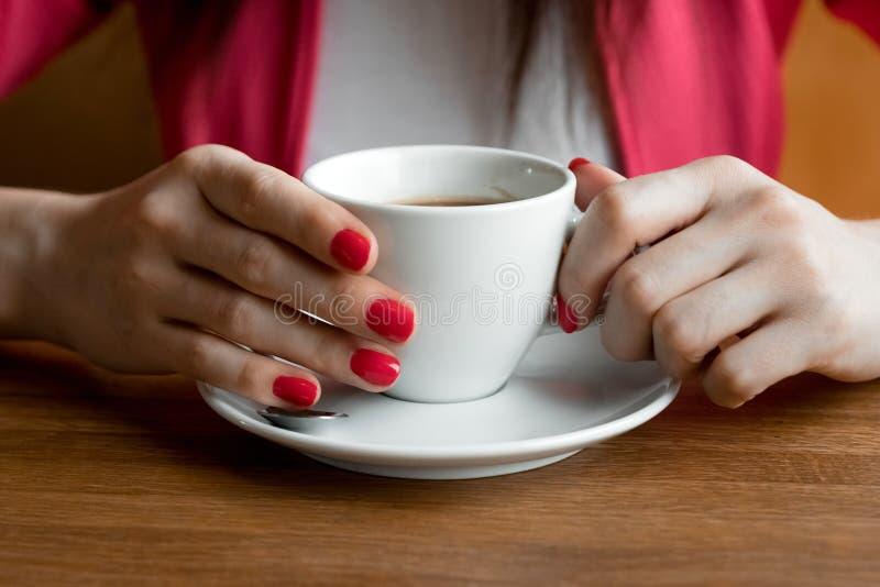 En kopp te eller kaffe i händerna på en kvinna, rosa manikyr, närliggande Begreppet kallt väder arkivbild
