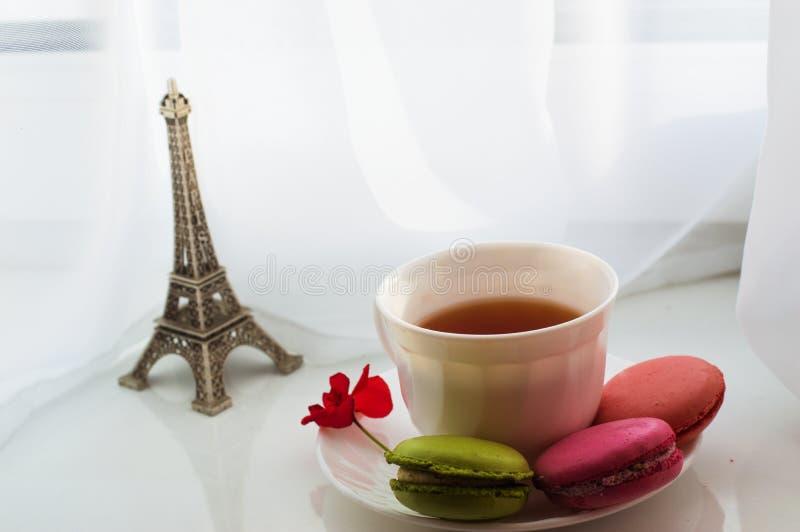 En kopp te, kakor och en blomma fotografering för bildbyråer