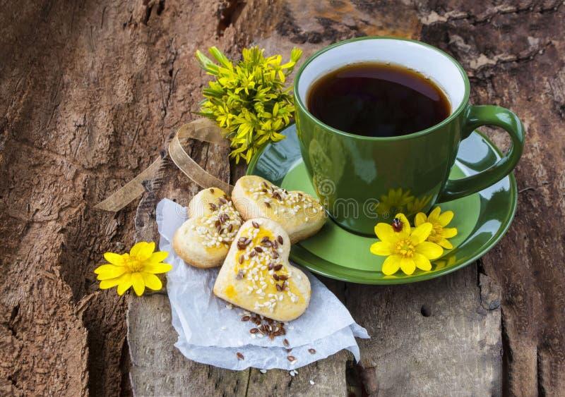 En kopp te med kakor på en träbakgrund royaltyfri foto