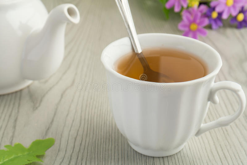 En kopp te och en tekanna royaltyfri bild