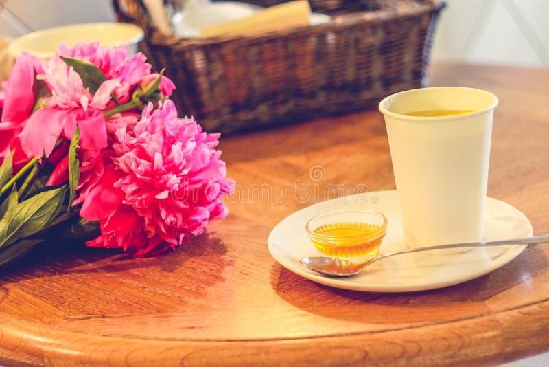 En kopp te och pioner, honung, sked vilar på tefatet, trätabellen, hemtrevligt hus arkivbild