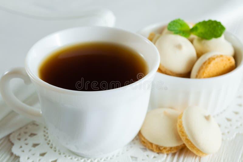En kopp te och små kakor med mintkaramellsidor på en vit trätabell arkivbild