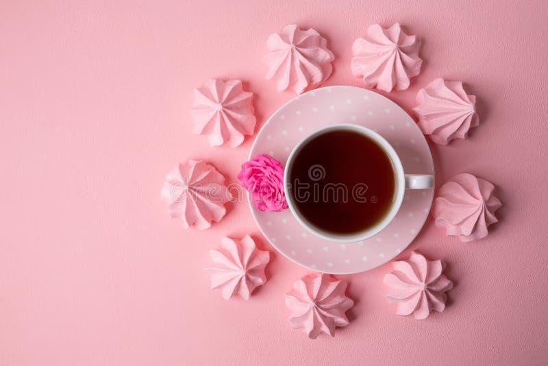En kopp te på en delikat rosa bakgrund arkivbild