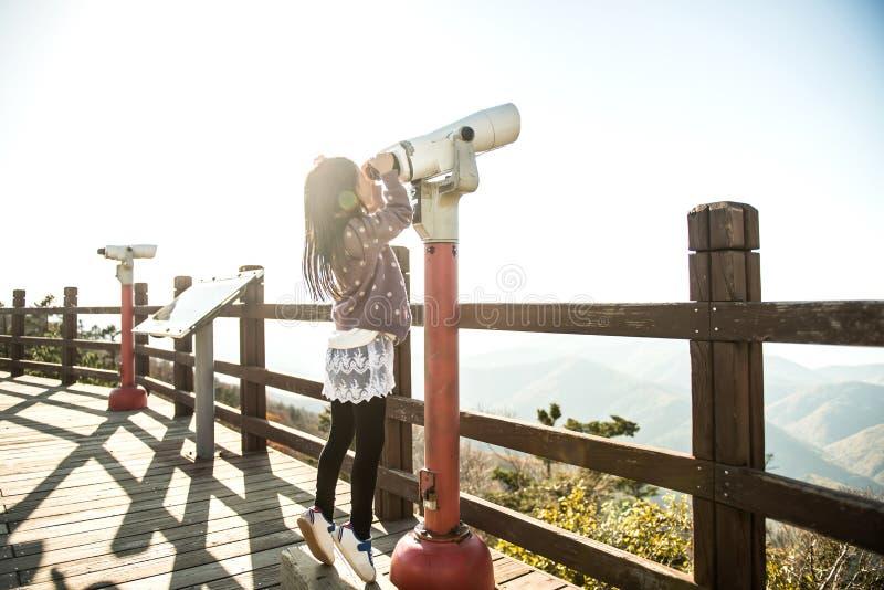En koreansk liten flicka som ser ett teleskop på en observatorium royaltyfri foto