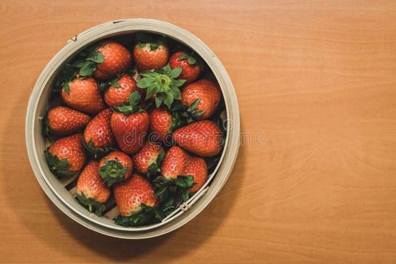 En korg mycket av härliga jordgubbar överst av en trätabell royaltyfri foto